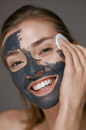 Beauty treatment. Woman taking off facial mask with cosmetic white pad. Girl model cleaning skin from grey clay mask closeup Stock Photo - 124606949