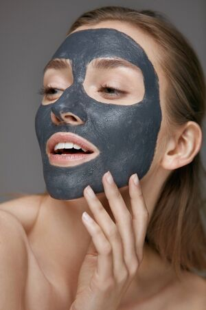 Skin care. Woman face with cosmetic spa clay mask closeup. Girl model with grey mask doing beauty spa treatment Stock Photo - 124620801