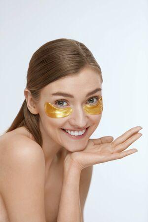Cura della pelle. Donna con macchie dorate sotto gli occhi, maschera di bellezza sul viso su sfondo bianco. Modello di ragazza sorridente felice con cuscinetti di collagene dorati Archivio Fotografico