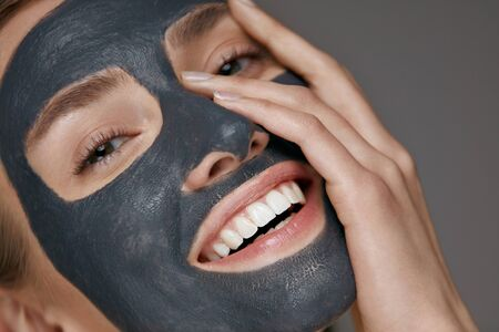 Beauty face skin care. Woman with cosmetic spa facial mask. Smiling girl model with grey clay mask and beautiful white smile closeup portrait Stock Photo - 124621156