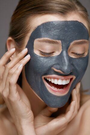 Beauty face skin care. Woman with cosmetic spa facial mask. Smiling girl model with grey clay mask and beautiful white smile closeup portrait Stock Photo