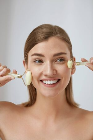 Beauty face care. Woman doing face massage with jade facial rollers for spa skin care treatment at home. Smiling girl using natural massager tool portrait