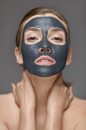 Hautpflege. Frauengesicht mit kosmetischer Spa-Ton-Maske-Nahaufnahme. Mädchenmodell mit grauer Maske, die Beauty-Spa-Behandlung macht
