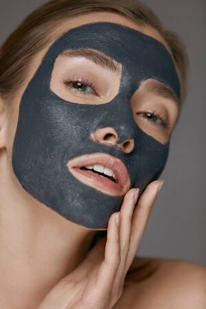 Skin care. Woman face with cosmetic spa clay mask closeup. Girl model with grey mask doing beauty spa treatment
