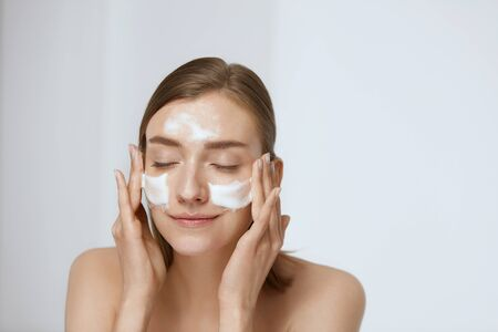 Cura della pelle del viso. Donna che applica detergente viso sul primo piano del viso. Ragazza che usa un prodotto cosmetico detergente sulla pelle, lava il viso su uno sfondo chiaro Archivio Fotografico