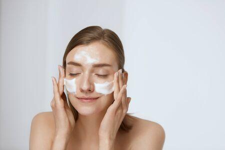 Gezicht huidverzorging. Vrouw die gezichtsreiniger op gezichtsclose-up toepast. Meisje met reinigend cosmetisch product op de huid, gezicht wassen op lichte achtergrond Stockfoto