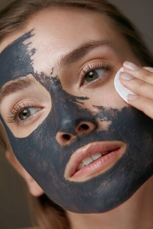 Beauty treatment. Woman taking off facial mask with cosmetic white pad. Girl model cleaning skin from grey clay mask closeup Stock Photo