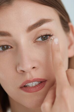 Contact eye lens. Woman applying eye contacts on hazel eyes closeup. Girl with natural face makeup inserting soft lenses on eye. Ophthalmology and vision care Stok Fotoğraf