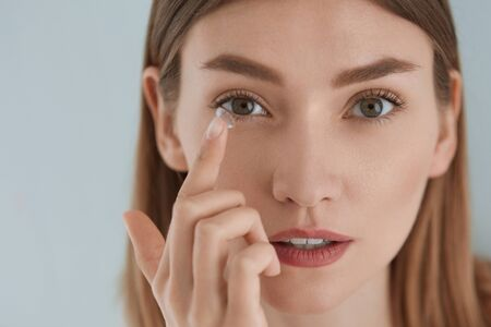 Lenti a contatto. Donna che applica i contatti oculari sul primo piano degli occhi nocciola. Ragazza con trucco viso naturale che inserisce lenti morbide sull'occhio. Oftalmologia e cura della vista