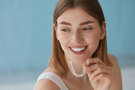 Blanqueamiento dental. Mujer con sonrisa blanca, dientes rectos sanos con tirantes extraíbles transparentes, bandeja de dientes invisibles. Retrato de niña haciendo tratamientos de belleza dental Foto de archivo