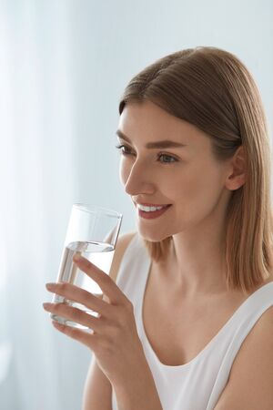 Drink. Woman drinking fresh pure water from glass portrait indoors. Beautiful girl with healthy skin with glass of mineral water on light background Stock fotó