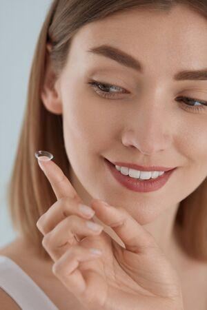Cura degli occhi. Donna sorridente con la lente dell'occhio a contatto sul primo piano del dito. Ritratto di bella ragazza che mette le lenti a contatto negli occhi. Concetto di salute della vista