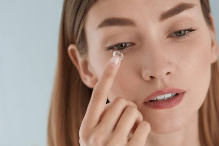 Contact eye lens. Woman applying eye contacts on hazel eyes closeup. Girl with natural face makeup inserting soft lenses on eye. Ophthalmology and vision care