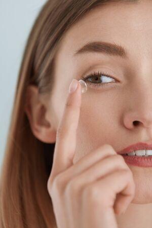 Kontaktlinsen augen. Frau, die Augenkontakte auf haselnussbrauner Augennahaufnahme anwendet. Mädchen mit natürlichem Gesichtsmake-up, das weiche Linsen auf das Auge einfügt. Augenheilkunde und Sehhilfe
