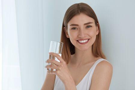 Femme avec un verre d'eau douce en portrait blanc. Belle fille souriante avec une peau saine et un visage de beauté tenant de l'eau minérale pure en verre à l'intérieur