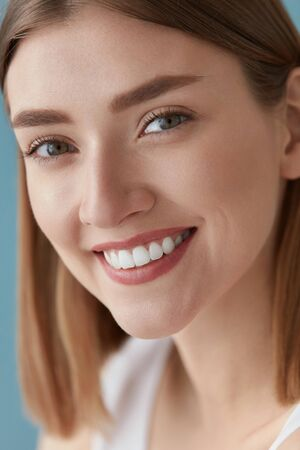 Smiling woman with beauty face and white teeth smile closeup. Happy girl with clean skin and natural makeup portrait