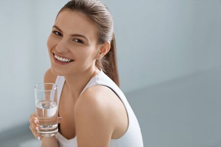 Drink water. Smiling woman holding fresh pure water in glass portrait indoors