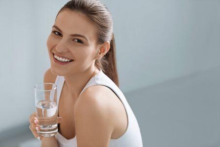 Wasser trinken. Lächelnde Frau mit frischem, reinem Wasser im Glasporträt drinnen