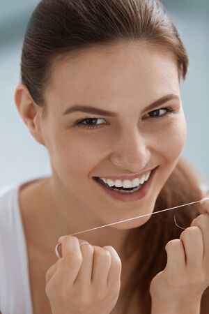 Dental care. Smiling woman cleaning white teeth with floss. Portrait of girl with beautiful smile flossing teeth for oral hygiene and tooth health Stock Photo