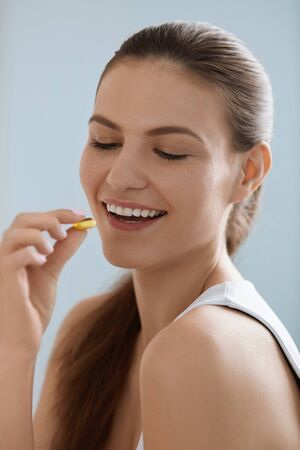 Vitamin. Smiling woman taking omega pill, fish oil supplement. Closeup portrait of beautiful girl eating capsule with vitamin D, E. Diet nutrition concept Stock Photo