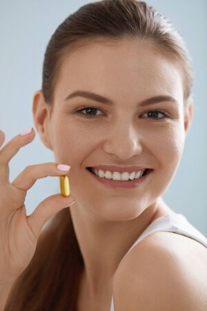 Vitamin. Smiling woman with omega 3 pill, fish oil capsule in hand. Closeup portrait of beautiful girl taking vitamin D, E supplement. Diet nutrition concept Stock Photo