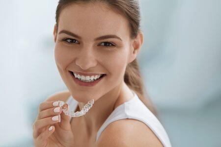 Blanqueamiento dental. Mujer con sonrisa blanca, dientes rectos sanos con tirantes extraíbles transparentes, bandeja de dientes invisibles. Retrato de niña haciendo tratamientos de belleza dental