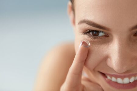 Contact eye lens. Smiling woman applying eye contacts on brown eyes closeup. Girl with natural face makeup inserting soft lenses. Ophthalmology and vision care