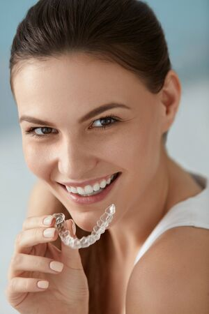 Dental care. Smiling woman with healthy teeth using removable clear braces aligner, orthodontic silicone trainer. Portrait girl with white smile using invisible whitening tray Standard-Bild