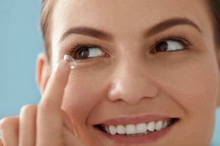Contact eye lens. Smiling woman applying eye contacts on brown eyes closeup. Girl with natural face makeup inserting soft lenses. Ophthalmology and vision care Stockfoto