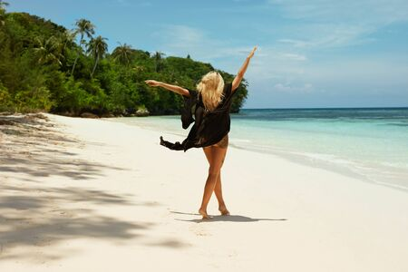 Summer vacation. Happy woman relaxing on tropical sand beach near sea. Beautiful girl with blonde hair and sexy tattooed legs in black beachwear dress with raised up hands walking on beach