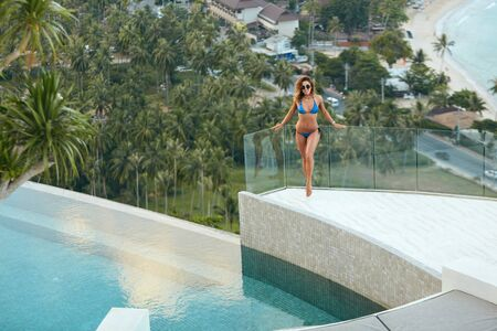 Woman on summer vacation at luxury resort near infinity pool with beautiful view. Girl in swimsuit near edge of villa at Thailand