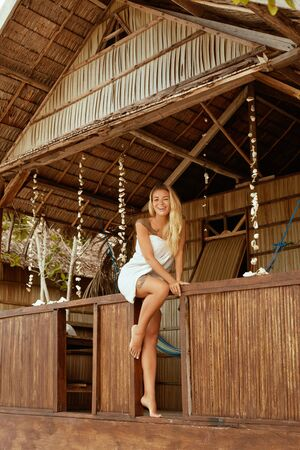 Smiling woman relaxing in beach bungalow at tropical resort on summer vacation. Beautiful happy girl in white bath robe sitting on terrace of wooden guesthouse