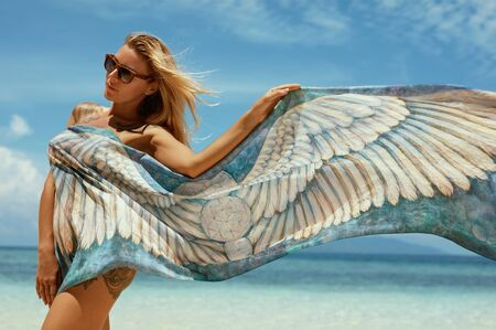 Woman in summer sunbathing on tropical beach on vacation. Beautiful girl model with blonde hair and sexy tattooed body in sunglasses and flying sarong scarf at luxury resort Imagens