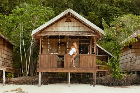 Mujer relajante en bungalow de playa en hotel tropical spa resort en vacaciones de verano. Hermosa niña feliz en bata de baño blanca sentada en la terraza de la casa de huéspedes de madera en Indonesia Foto de archivo