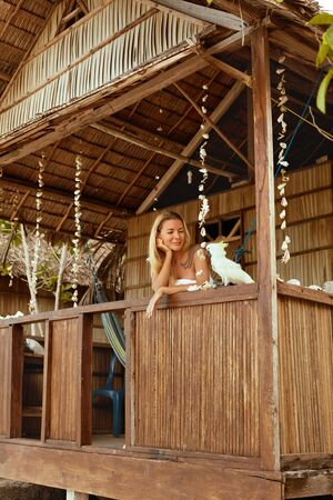 Woman with parrot in bungalow at tropical resort on summer vacation. Beautiful happy girl relaxing with bird on porch of wooden guesthouse in Indonesia