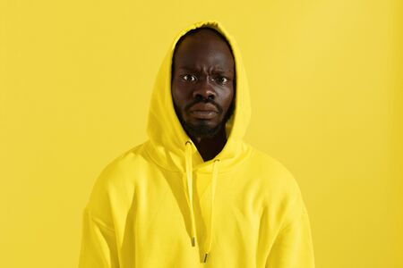Black man in yellow hoodie with shocked face expression on color background. Surprised african american male model in stylish sweatshirt with hood on head in studio