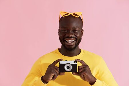 Happy man photographer with photo camera on colorful pink background. Portrait of smiling black male model in yellow fashion clothes taking photos in studio Stock Photo