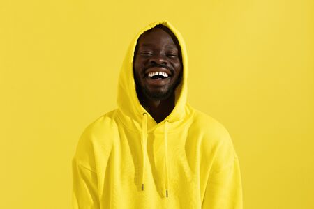 Portrait of happy black man in yellow hoodie on color background. Cheerful smiling african american male model with white smile in stylish sweatshirt with hood on head in studio