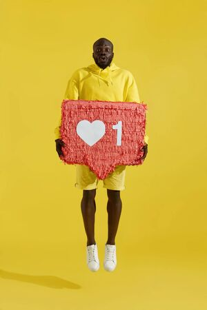Like. Surprised black man jumping with like heart icon pinata on yellow background. Full-length photo of amazed male model with huge like sign button jump in air Stock Photo