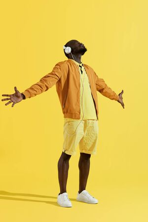 Man in headphones and fashion clothes listening music, singing on yellow background. Full length portrait of black male model in white earphones enjoying song