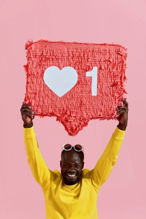 Like. Happy black man holding like heart icon pinata on pink background. Smiling male model in yellow fashion clothes demonstrating like sign button, social media symbol Stock Photo