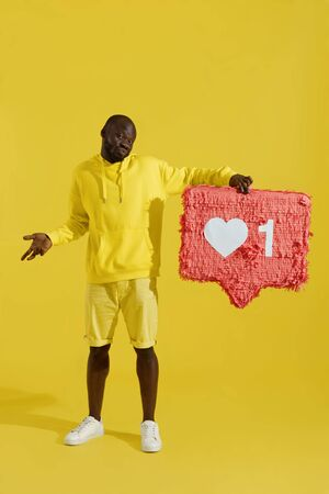 Like. Disappointed man holding heart icon pinata on yellow background. Black male model with huge like sign button, social media symbol