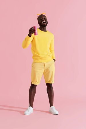 Drink. Happy black man in yellow fashion clothes with soft drink on pink background. Cheerful smiling young african american male model holding pink soda can in studio
