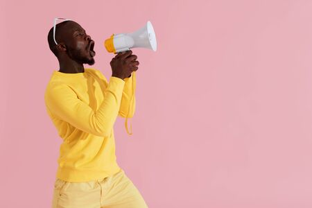 Black man shouting in megaphone on pink background portrait. Happy young male model screaming in horn speaker in studio Stock Photo