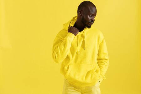 Fashion portrait of black man in yellow hoodie on color background. Handsome african american male model in stylish sweatshirt with hood posing in studio