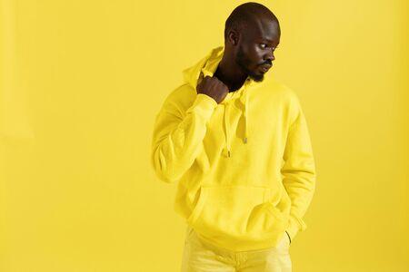 Mode portret van zwarte man in gele hoodie op kleur achtergrond. Knappe Afro-Amerikaanse mannelijk model in stijlvol sweatshirt met capuchon poseren in studio Stockfoto