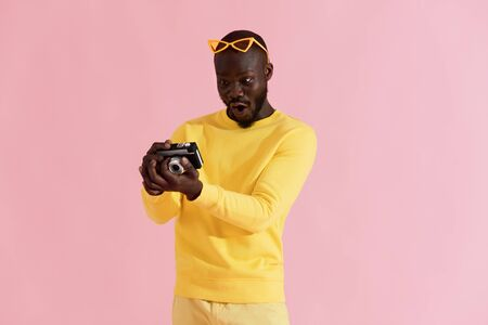 Surprised man looking on photos on camera on colorful pink background. Portrait of amazed shocked black male photographer in yellow fashion clothes with photo camera