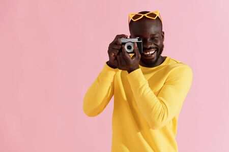 Happy man photographer with photo camera on colorful pink background. Portrait of smiling black male model in yellow fashion clothes taking photos in studio Фото со стока