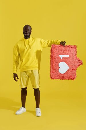 Like. Happy black man holding like heart icon pinata on yellow background. Smiling male model in fashion clothes with huge like sign button