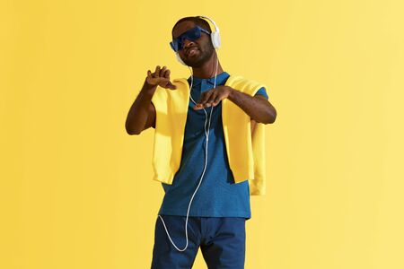 Man in headphones listening music and dancing on yellow background portrait. Happy black male model in headphone, sunglasses and fashion clothes in studio
